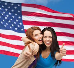 Bild på skrattande tjejer framför en USA-flagga