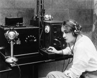 Kvinna som använder en telegraf för att kommunicera genom att använda morsekod.